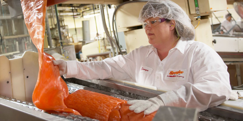 Employee watches Orange Dum Dums in the batch roller