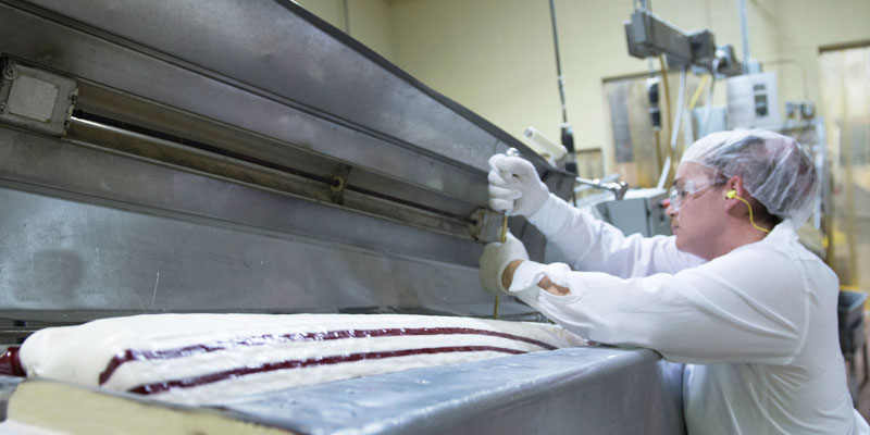 Employee monitors candy cane in the batch roller